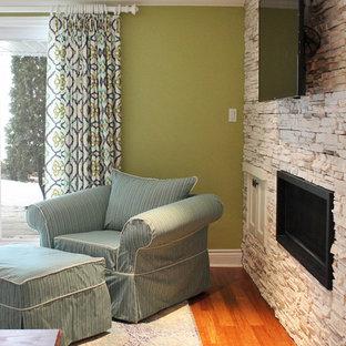 Réalisation d'un grand sous-sol tradition donnant sur l'extérieur avec un mur vert, un sol en bois brun, une cheminée standard et un manteau de cheminée en pierre.