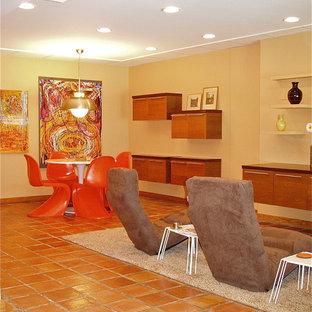 Cette photo montre un grand sous-sol moderne donnant sur l'extérieur avec un mur jaune et un sol en carreau de terre cuite.