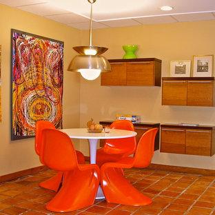 Inspiration pour un grand sous-sol bohème donnant sur l'extérieur avec un mur jaune et un sol orange.
