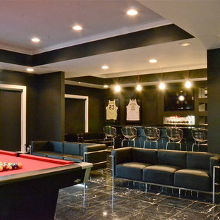 Example of a large minimalist black floor basement design in Charlotte with black walls