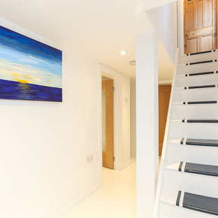 Idée de décoration pour un sous-sol design semi-enterré et de taille moyenne avec un mur blanc et un sol en bois peint.