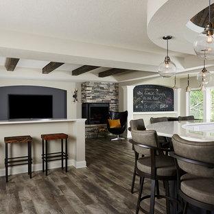 Inspiration pour un grand sous-sol traditionnel donnant sur l'extérieur avec un mur gris, un sol en vinyl, un manteau de cheminée en pierre, un sol gris et une cheminée d'angle.