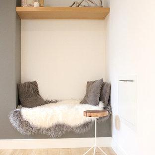 Aménagement d'un sous-sol scandinave semi-enterré et de taille moyenne avec un mur blanc et un sol en bois clair.