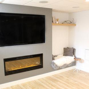 Aménagement d'un sous-sol scandinave semi-enterré et de taille moyenne avec un mur blanc, un sol en bois clair, une cheminée ribbon et un sol beige.