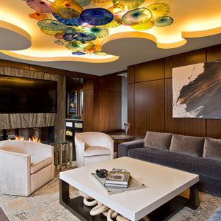 Cette image montre un très grand sous-sol design enterré avec un mur marron, un sol en bois foncé, une cheminée double-face, un manteau de cheminée en pierre et un sol marron.