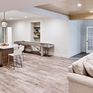 Inspiration pour un grand sous-sol traditionnel donnant sur l'extérieur avec un mur blanc, cheminée suspendue et un sol gris.