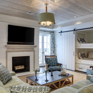Inspiration for a mid-sized beach style walk-out dark wood floor and brown floor basement remodel in New York with white walls and a standard fireplace