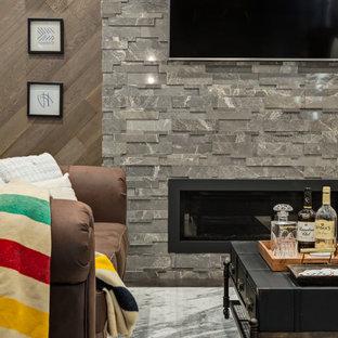 Idée de décoration pour un sous-sol design avec béton au sol, une cheminée standard, un manteau de cheminée en pierre de parement et un sol gris.