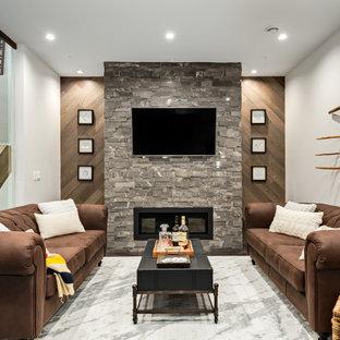 Exemple d'un sous-sol tendance avec béton au sol, une cheminée standard, un manteau de cheminée en pierre de parement et un sol gris.