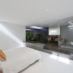 Idée de décoration pour un grand sous-sol design enterré avec un mur blanc et un sol blanc.