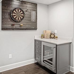 Réalisation d'un très grand sous-sol tradition semi-enterré avec un mur gris, un sol en vinyl, une cheminée standard, un manteau de cheminée en pierre et un sol gris.