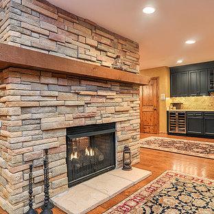 Idées déco pour un grand sous-sol montagne enterré avec un mur beige, un sol en bois brun, une cheminée double-face et un manteau de cheminée en pierre.