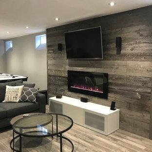 Cette photo montre un sous-sol tendance enterré et de taille moyenne avec un mur gris, sol en stratifié, une cheminée standard, un manteau de cheminée en bois et un sol gris.