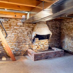 Exemple d'un petit sous-sol montagne avec un manteau de cheminée en pierre.