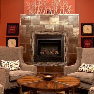 Ispirazione per una taverna moderna interrata di medie dimensioni con pareti arancioni, parquet scuro, camino classico, cornice del camino in metallo e pavimento marrone