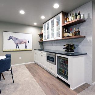 Réalisation d'un grand sous-sol minimaliste semi-enterré avec un mur gris, moquette, une cheminée double-face, un manteau de cheminée en bois et un sol beige.