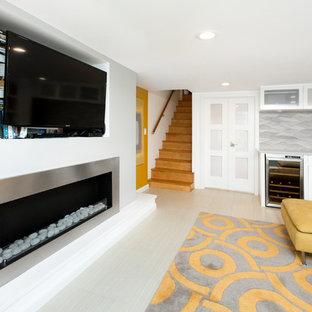 Aménagement d'un grand sous-sol contemporain donnant sur l'extérieur avec un mur blanc, une cheminée ribbon et un manteau de cheminée en métal.