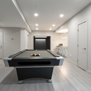 Cette image montre un très grand sous-sol design donnant sur l'extérieur avec un mur gris, sol en stratifié, aucune cheminée et un sol gris.
