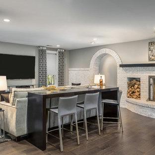 Ispirazione per una taverna moderna di medie dimensioni con sbocco, pareti grigie, pavimento in legno massello medio, camino classico, cornice del camino in mattoni e pavimento marrone