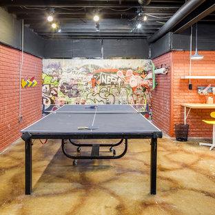 Foto di una grande taverna industriale interrata con pareti marroni, pavimento in cemento e pavimento multicolore