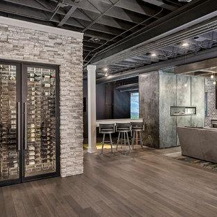 Exemple d'un grand sous-sol tendance enterré avec un mur beige, un sol en bois brun, une cheminée ribbon, un manteau de cheminée en métal et un sol marron.