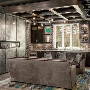 Idée de décoration pour un grand sous-sol design enterré avec un mur beige, un sol en bois brun, une cheminée ribbon, un manteau de cheminée en métal et un sol marron.