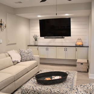 Inspiration for a large country look-out vinyl floor and gray floor basement remodel in Detroit with gray walls