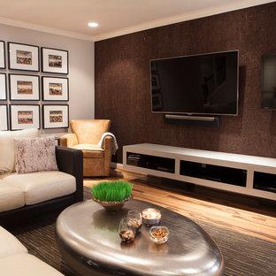 Réalisation d'un grand sous-sol design donnant sur l'extérieur avec un mur gris, un sol en bois brun et aucune cheminée.