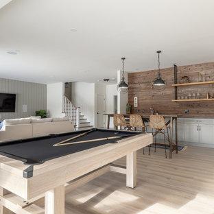 Aménagement d'un grand sous-sol classique donnant sur l'extérieur avec un mur multicolore, sol en stratifié, aucune cheminée, un sol beige et salle de jeu.