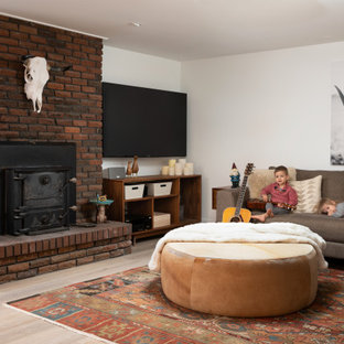 Esempio di una taverna minimalista con sbocco, pareti bianche, pavimento in laminato, stufa a legna e cornice del camino in mattoni