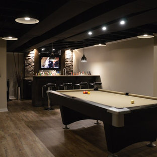 Example of a large minimalist underground vinyl floor and brown floor basement design in Detroit with beige walls and no fireplace
