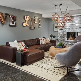 Cette photo montre un grand sous-sol moderne avec un mur gris, une cheminée standard, un manteau de cheminée en pierre et un sol noir.