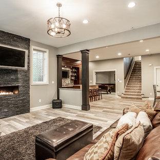 Idées déco pour un grand sous-sol classique semi-enterré avec un mur gris, un sol en vinyl, un manteau de cheminée en pierre, une cheminée ribbon et un sol beige.