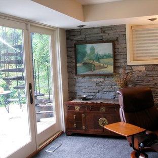 Cette image montre un grand sous-sol rustique donnant sur l'extérieur avec un bar de salon, moquette, un sol noir et un plafond décaissé.