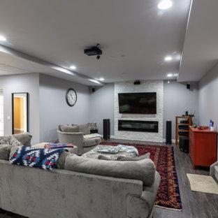 Cette image montre un grand sous-sol traditionnel donnant sur l'extérieur avec un mur gris, un sol en vinyl, une cheminée ribbon, un manteau de cheminée en pierre et un sol gris.
