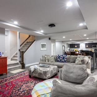 Aménagement d'un grand sous-sol classique donnant sur l'extérieur avec un mur gris, un sol en vinyl, une cheminée ribbon, un manteau de cheminée en pierre et un sol gris.
