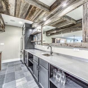 Réalisation d'un sous-sol design semi-enterré avec un mur gris et un sol en ardoise.