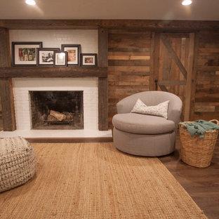 Cette image montre un grand sous-sol chalet semi-enterré avec un mur marron, un sol en bois brun, une cheminée standard, un manteau de cheminée en brique et un sol marron.