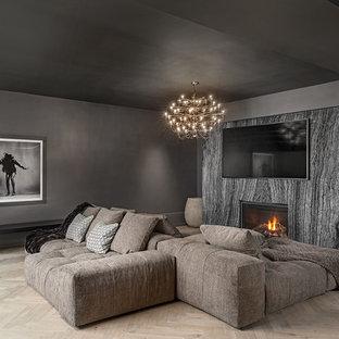 Idée de décoration pour un sous-sol méditerranéen avec un mur noir, un sol en bois clair, une cheminée standard, un manteau de cheminée en pierre et un sol beige.