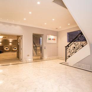Aménagement d'un sous-sol classique avec un sol en marbre et un sol blanc.