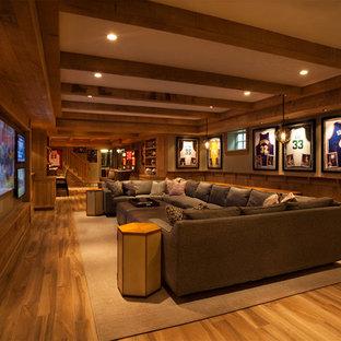 Réalisation d'un très grand sous-sol tradition avec un mur beige, un sol en bois brun, aucune cheminée et un sol jaune.