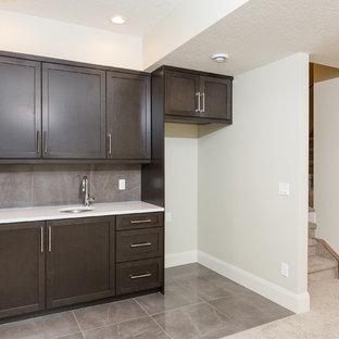 Réalisation d'un sous-sol design enterré et de taille moyenne avec un mur beige, un sol en marbre, aucune cheminée et un sol gris.