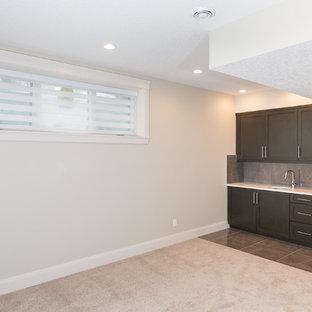 Idée de décoration pour un sous-sol design enterré et de taille moyenne avec un mur beige, un sol en marbre, aucune cheminée et un sol gris.