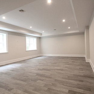 Inspiration for a large coastal walk-out medium tone wood floor and brown floor basement remodel in New York with gray walls, a standard fireplace and a metal fireplace