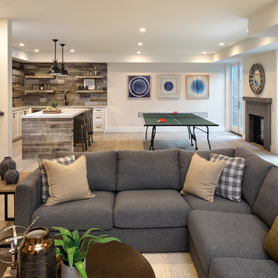 Inspiration for a large farmhouse walk-out ceramic tile and gray floor basement remodel in San Francisco with a stone fireplace, beige walls and a standard fireplace