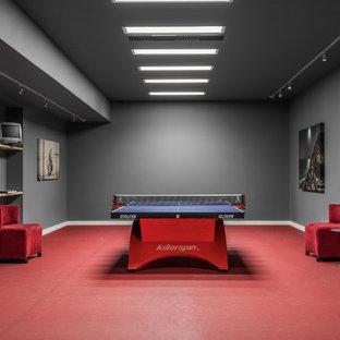Aménagement d'un sous-sol moderne donnant sur l'extérieur et de taille moyenne avec un mur gris et un sol rouge.