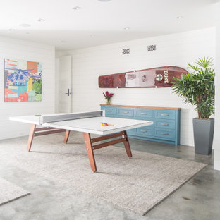 Example of a large beach style underground concrete floor and gray floor basement design in Orange County with white walls