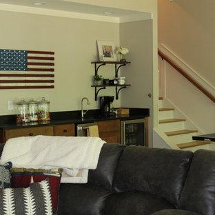 Cette image montre un sous-sol craftsman donnant sur l'extérieur et de taille moyenne avec un mur gris, un sol marron et un sol en bois brun.