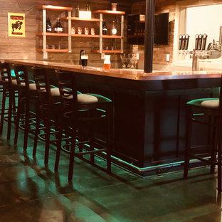 Inspiration pour un grand sous-sol traditionnel avec un bar de salon, béton au sol et un plafond en poutres apparentes.
