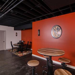 Cette photo montre un grand sous-sol industriel avec un bar de salon, un mur orange, béton au sol et un plafond en poutres apparentes.